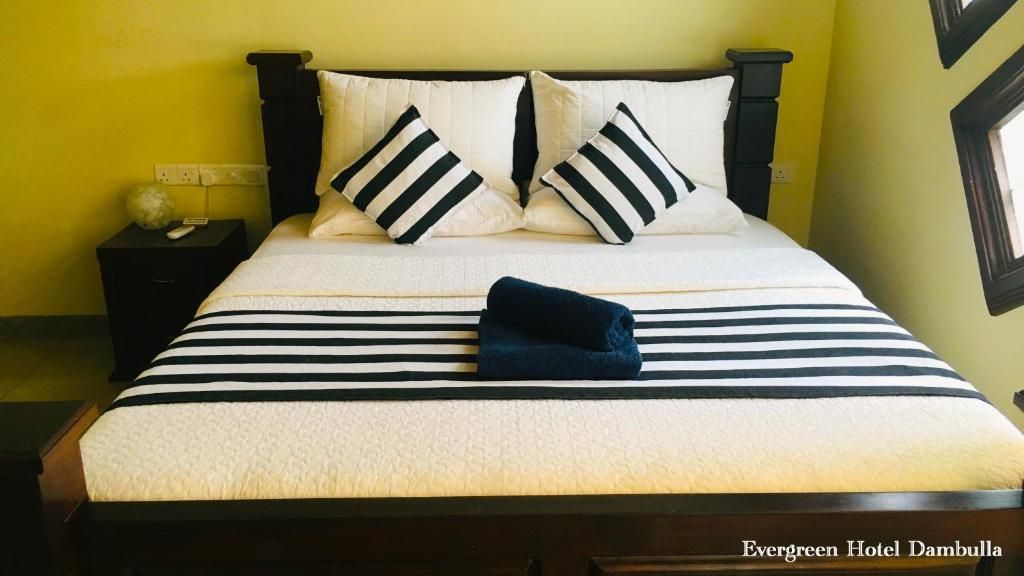 A bed or beds in a room at Evergreen Hotel Dambulla