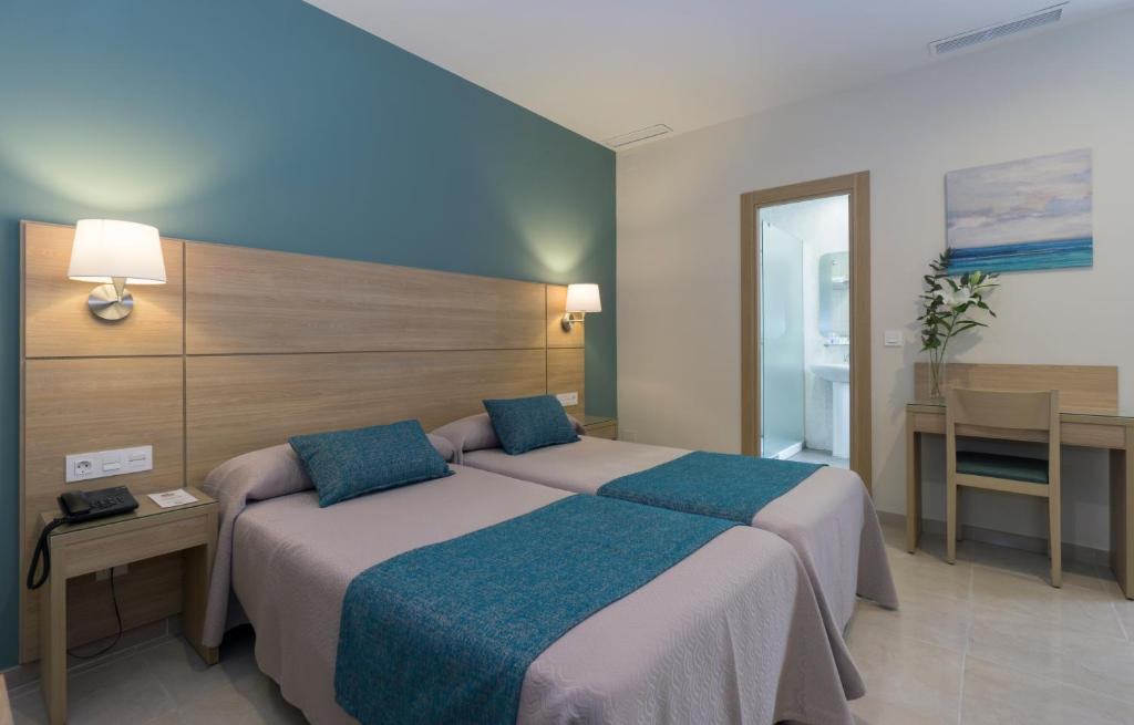 A bed or beds in a room at Hotel Sur Málaga