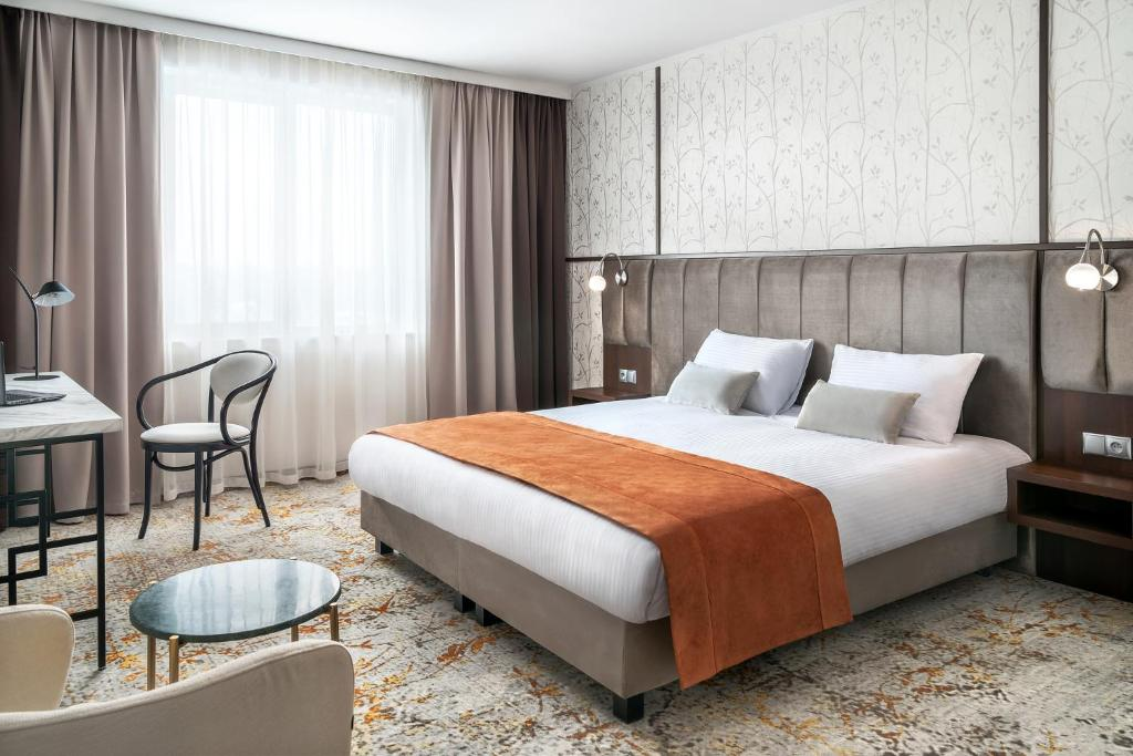 A bed or beds in a room at Metropolo by Golden Tulip Krakow