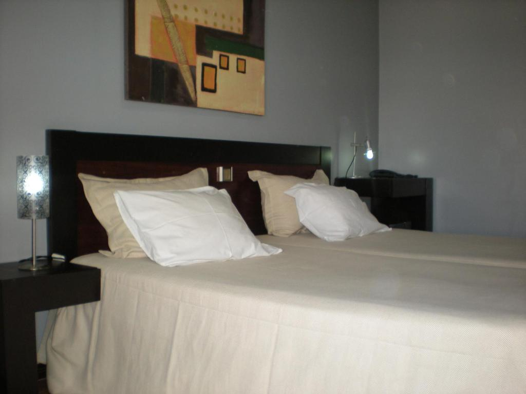 A bed or beds in a room at Hotel Dom Joao IV