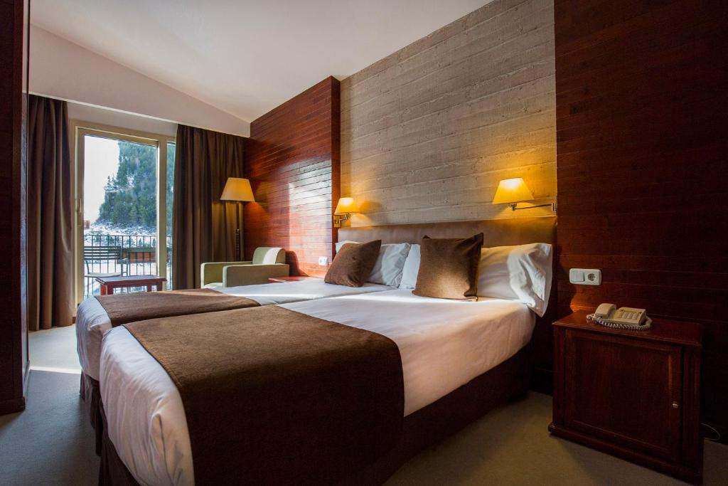A bed or beds in a room at Hotel Piolets Soldeu Centre