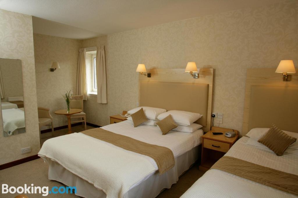 Een bed of bedden in een kamer bij New County Hotel