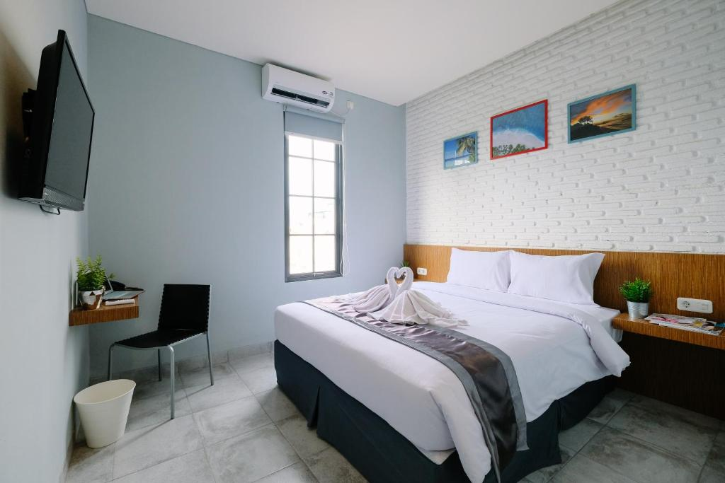 A bed or beds in a room at Lopi Hotel Makassar