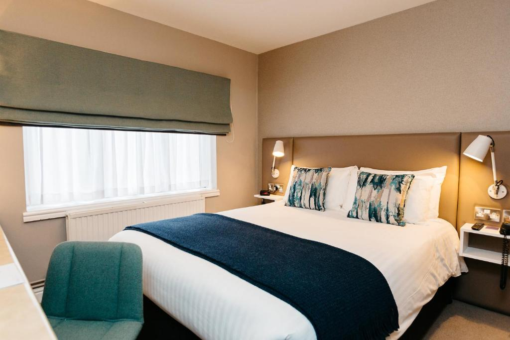A bed or beds in a room at Lucas House Hotel