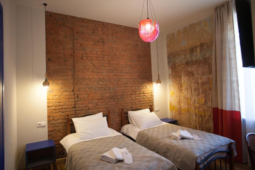 A bed or beds in a room at Bricks Room Hotel
