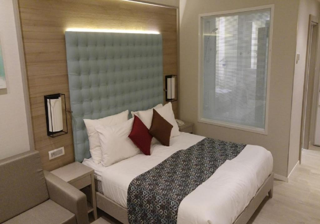 A bed or beds in a room at Astral Village Hotel