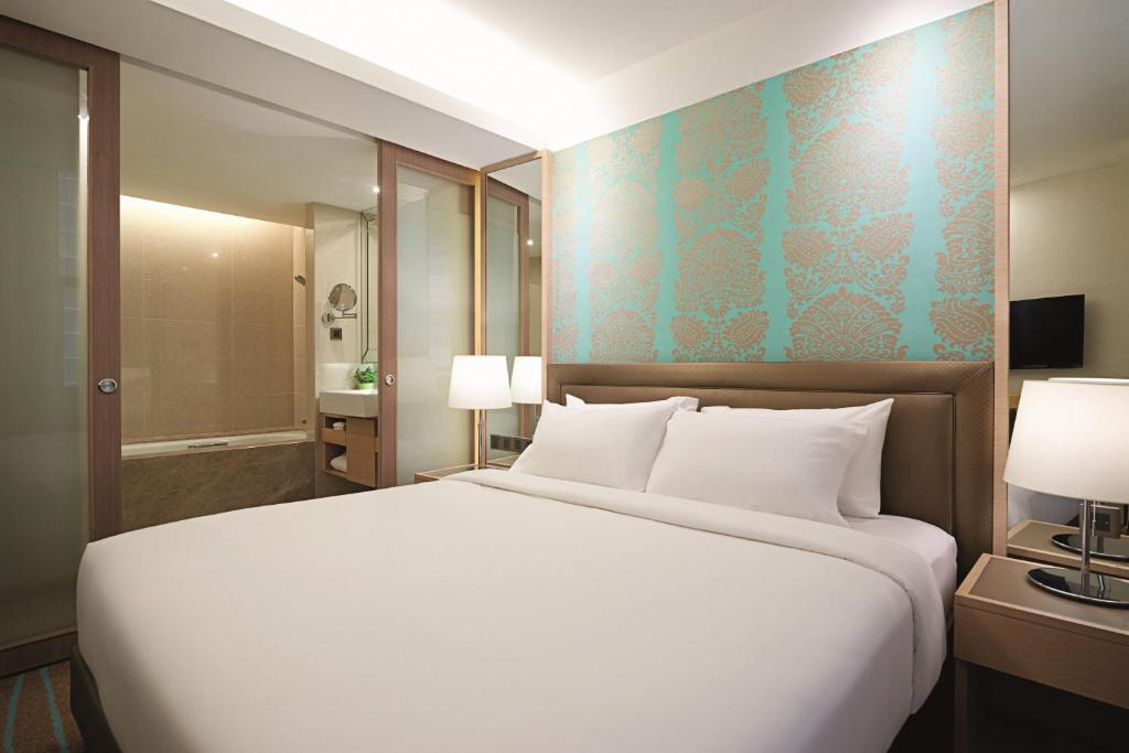 A bed or beds in a room at Cosmo Hotel Kuala Lumpur