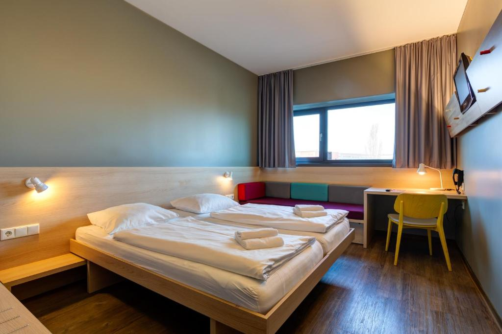 A bed or beds in a room at MEININGER Hotel Berlin Airport