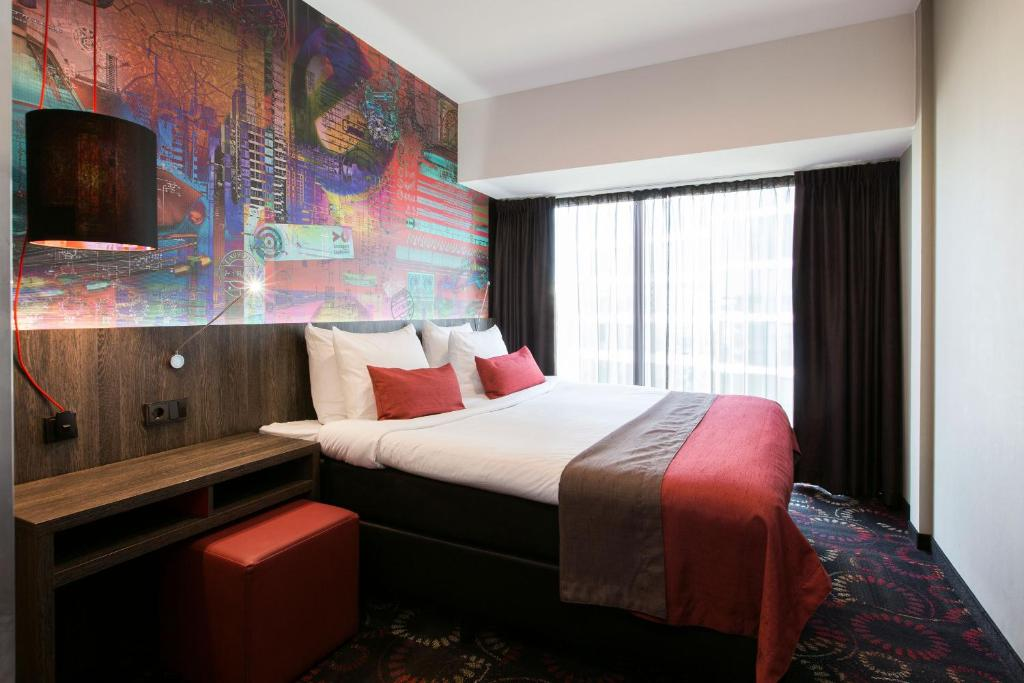 A bed or beds in a room at Crown Hotel Eindhoven Centre