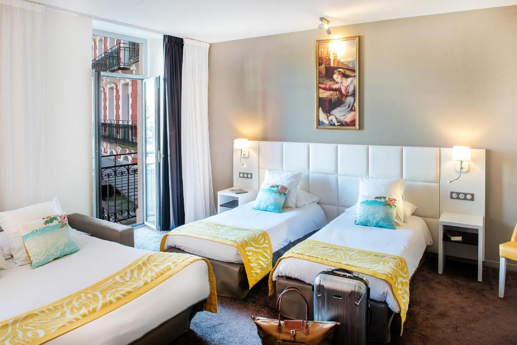 A bed or beds in a room at Grand Hôtel Gallia Chapelle & Spa NUXE