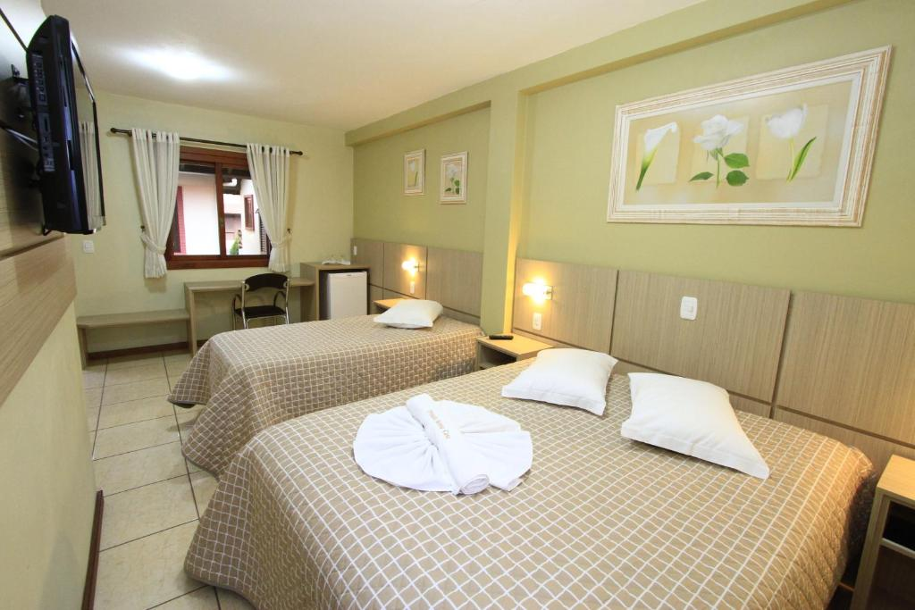 A bed or beds in a room at Pousada Floratta Nossa Casa