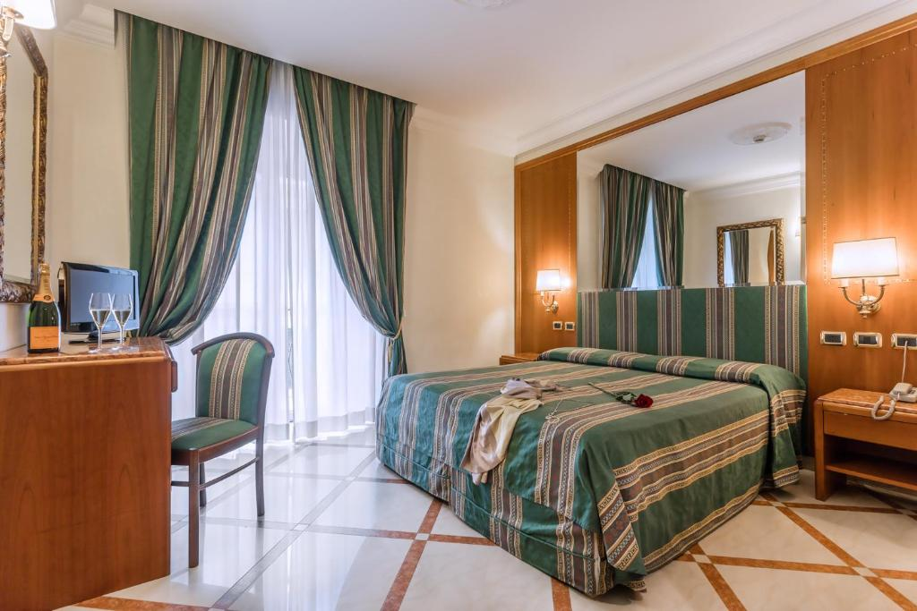 A bed or beds in a room at Raeli Hotel Regio