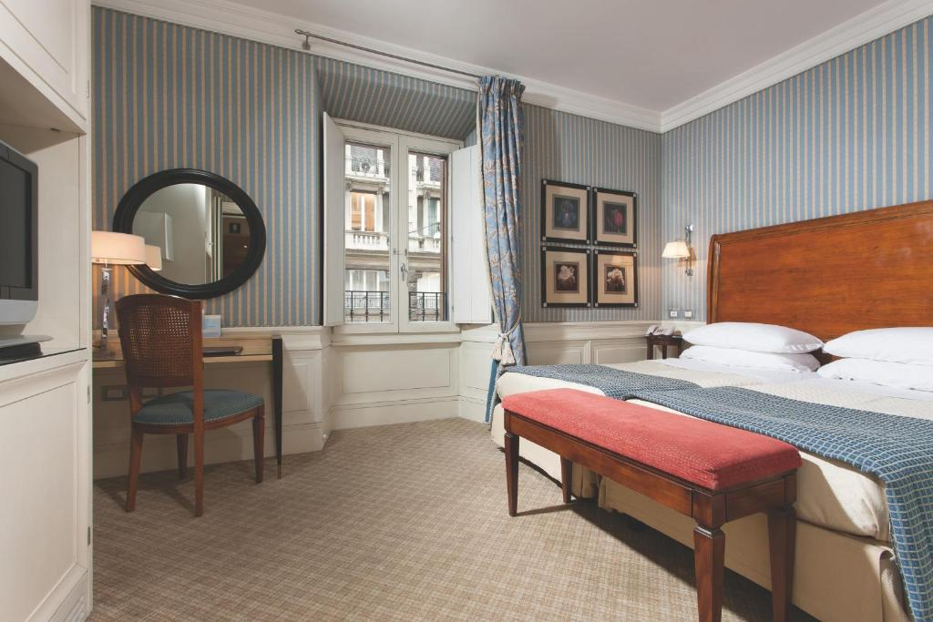A bed or beds in a room at Stendhal Hotel