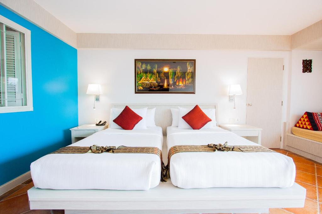 A bed or beds in a room at Karon Sea Sands Resort & Spa