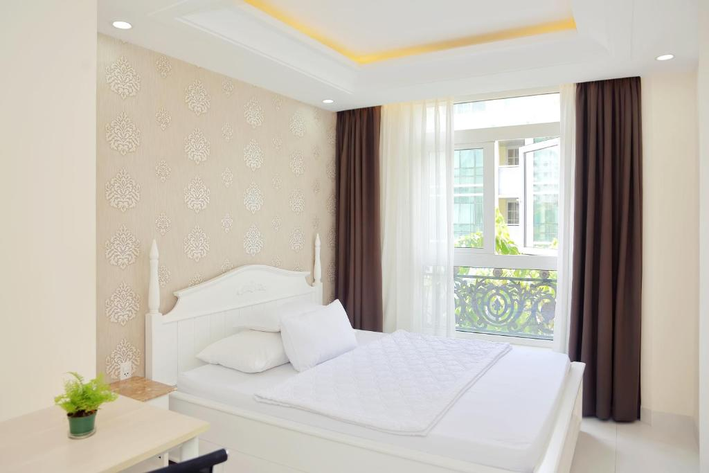 A bed or beds in a room at Sunshine Hotel - Phu My Hung