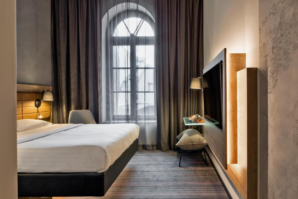 A bed or beds in a room at Moxy Warsaw Praga