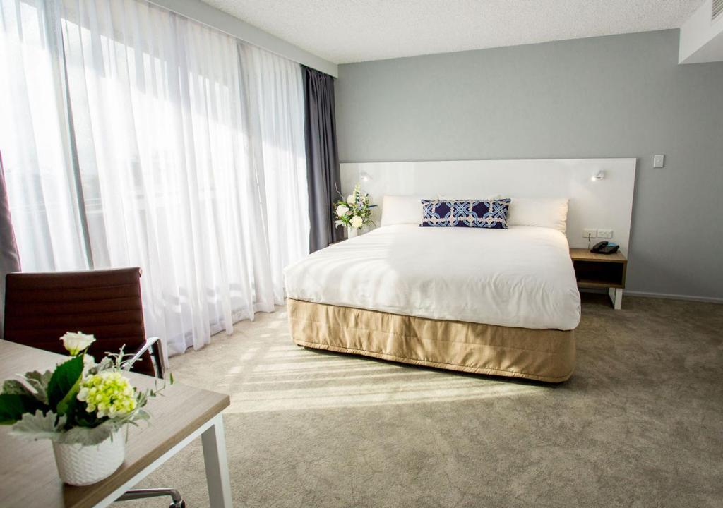 Ein Bett oder Betten in einem Zimmer der Unterkunft Pacific Hotel Brisbane