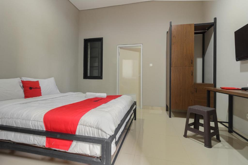 Tempat tidur dalam kamar di RedDoorz near Puri Indah Mall