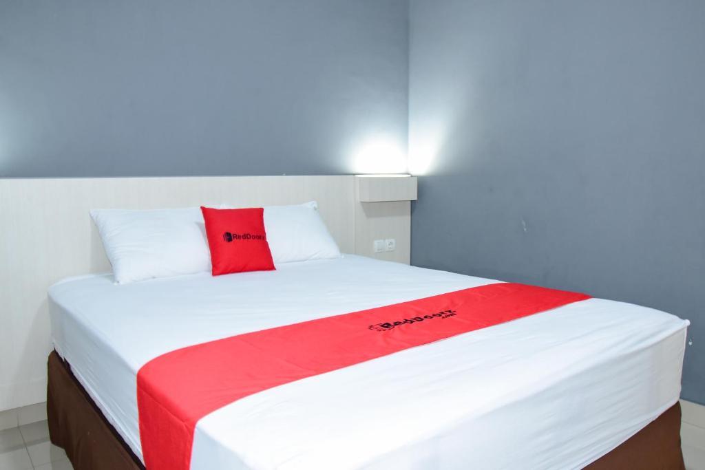 A bed or beds in a room at RedDoorz Syariah near Puro Pakulaman Palace