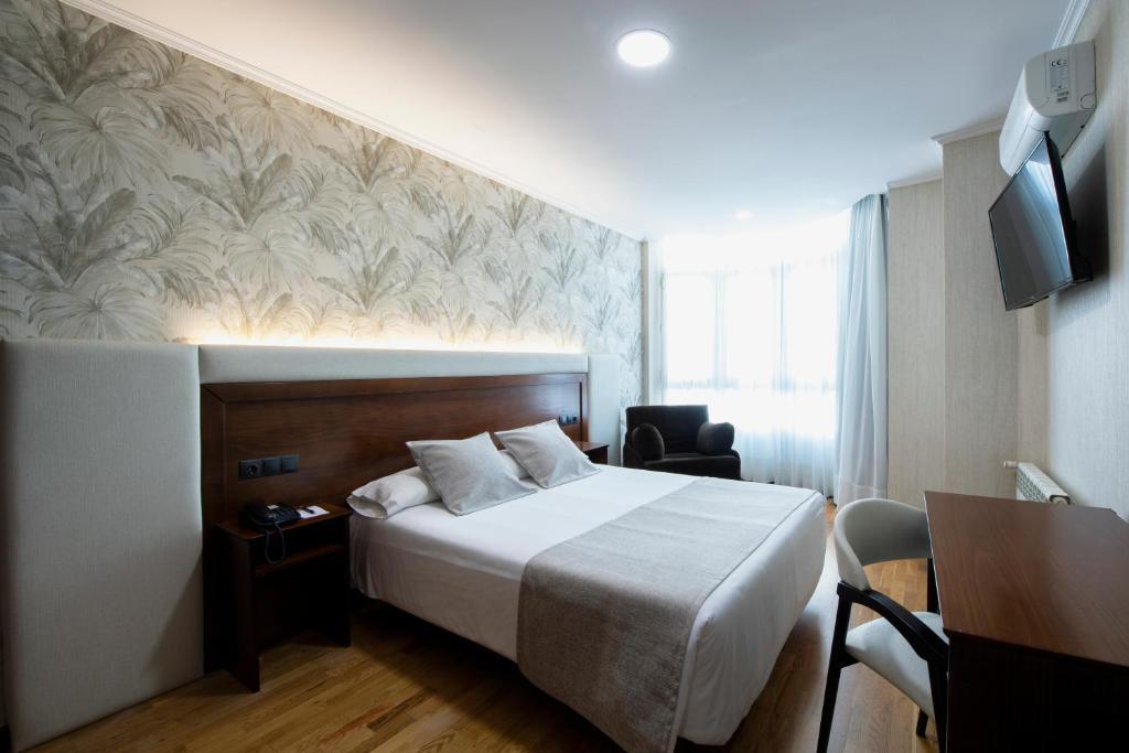 A bed or beds in a room at Hotel Oca Insua Costa da Morte
