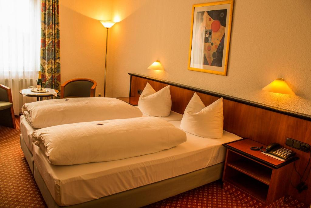 A bed or beds in a room at Hotel Schmaus