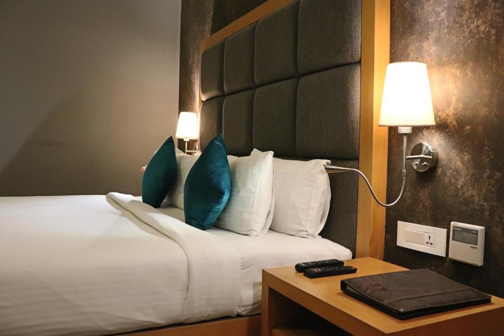 Łóżko lub łóżka w pokoju w obiekcie Crimson Park Shree Kanak