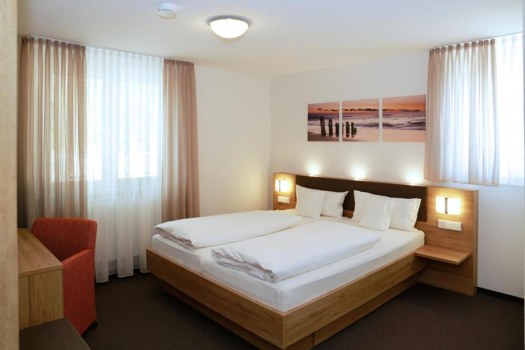 A bed or beds in a room at Hotel Gasthof Schützen