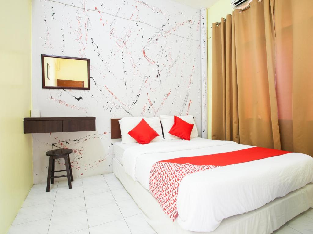 A bed or beds in a room at OYO 796 JR Hotel