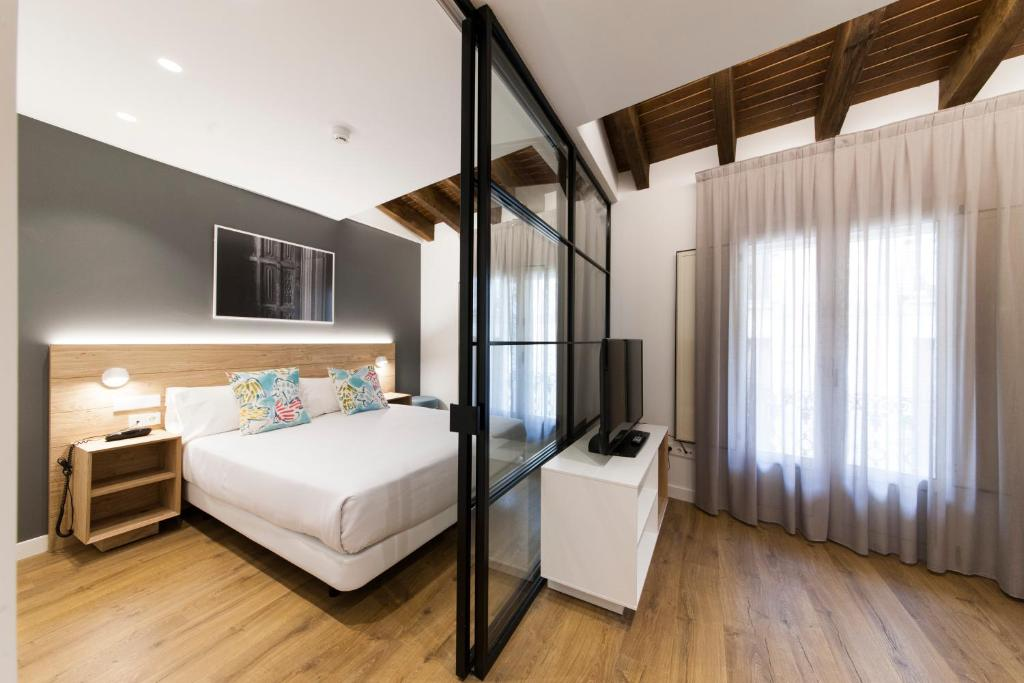 A bed or beds in a room at Antique Pamplona Tres Reyes Apartments