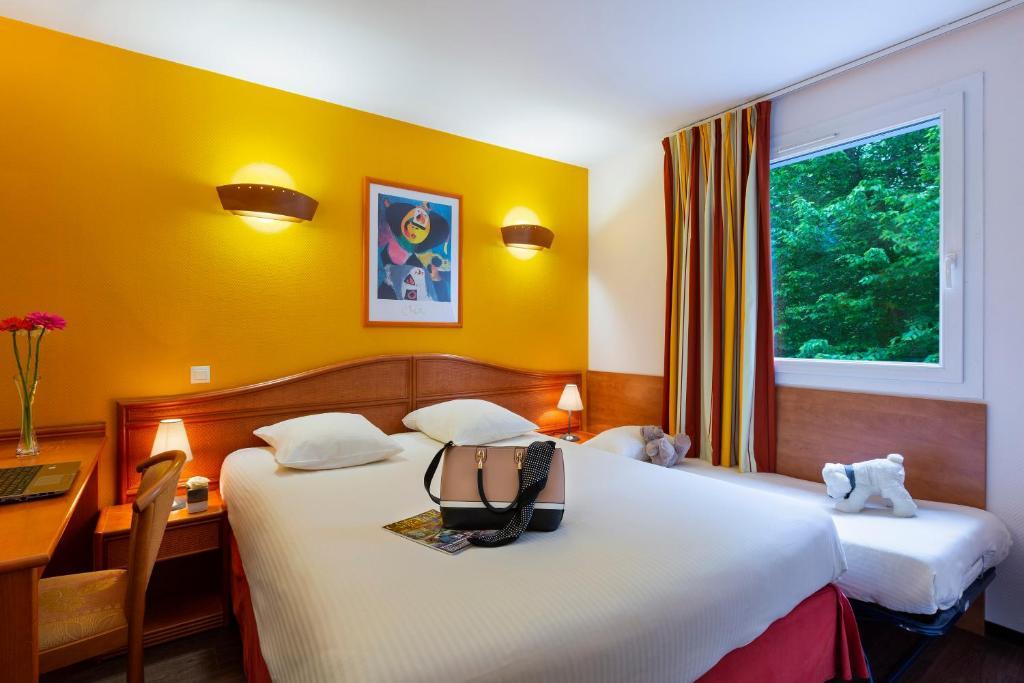 Un ou plusieurs lits dans un hébergement de l'établissement Hotel Roi Soleil - Amnéville