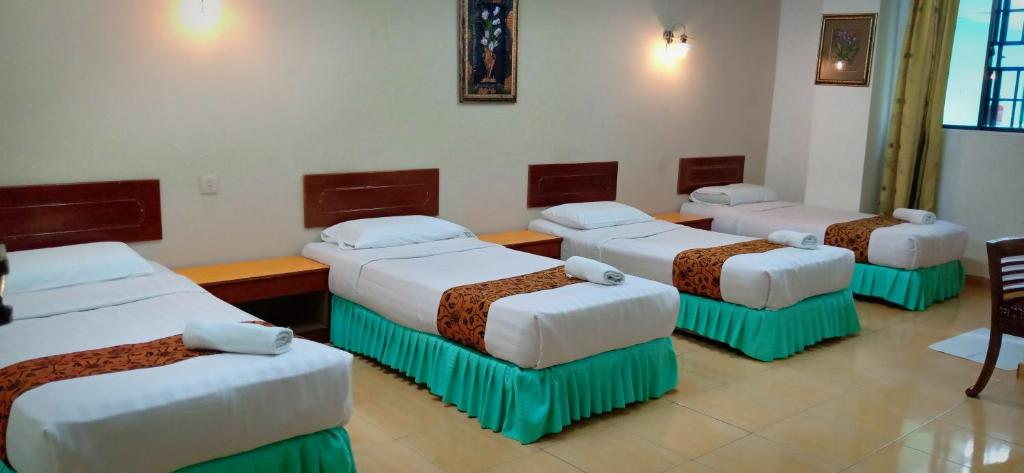 A bed or beds in a room at Hotel K T Mutiara