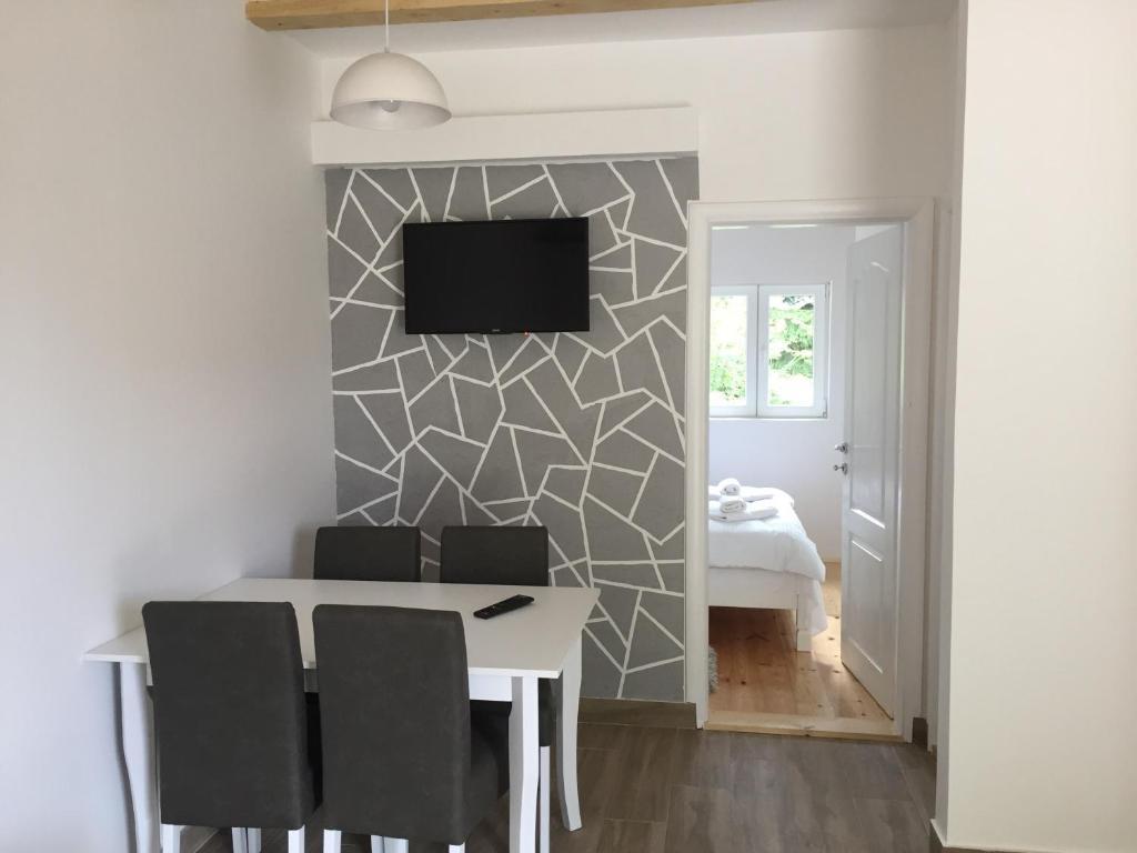 Una televisión o centro de entretenimiento en Guest House Dzakovic Stana