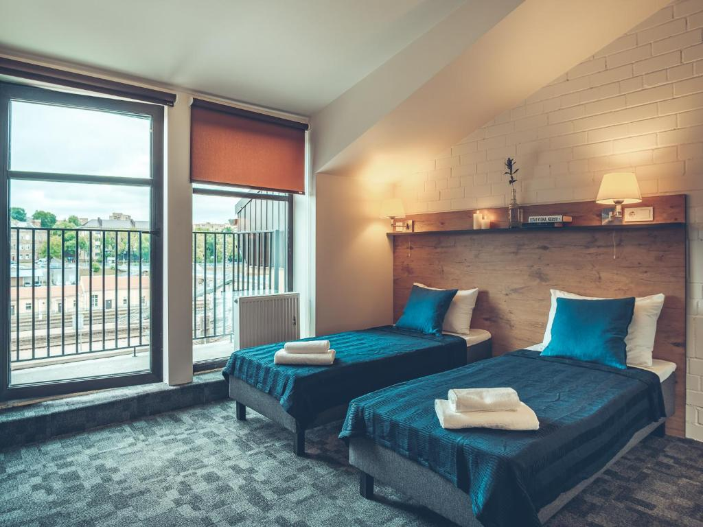 A bed or beds in a room at Railway Apartments & Hotel