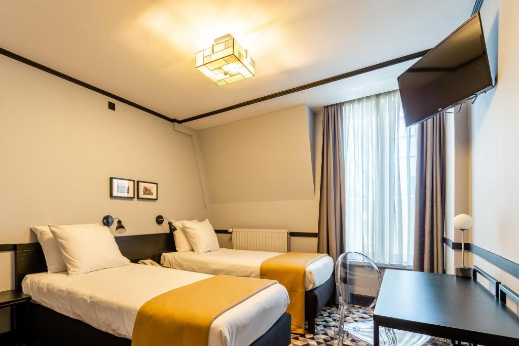 A bed or beds in a room at Hotel Des Colonies