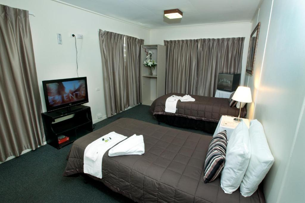 A bed or beds in a room at O'Sheas Windsor Hotel