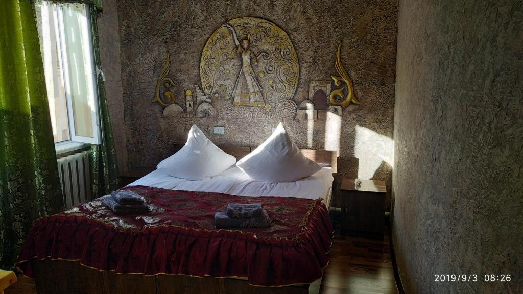A bed or beds in a room at Mubina Khiva B&B