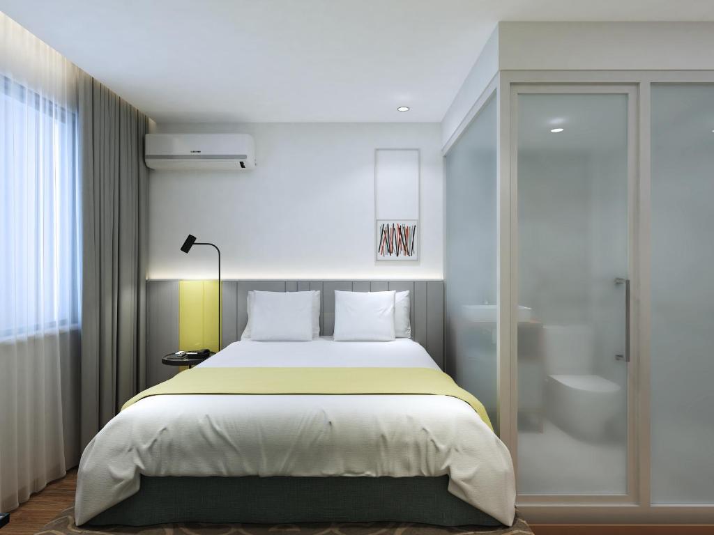 Una cama o camas en una habitación de Happy Dragon City Center Alley Hotel Forbidden City