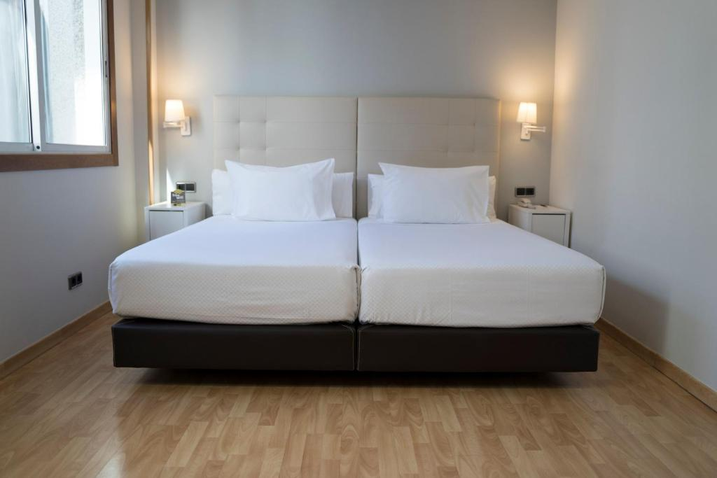 A bed or beds in a room at Hotel Sercotel Tres Luces