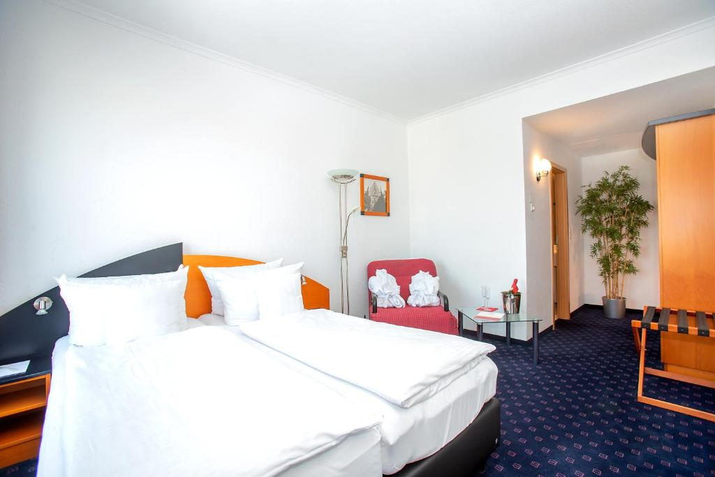 A bed or beds in a room at H&S Hotel Belmondo Leipzig - Airport