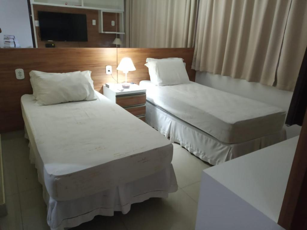 A bed or beds in a room at Ponta Verde Suíte