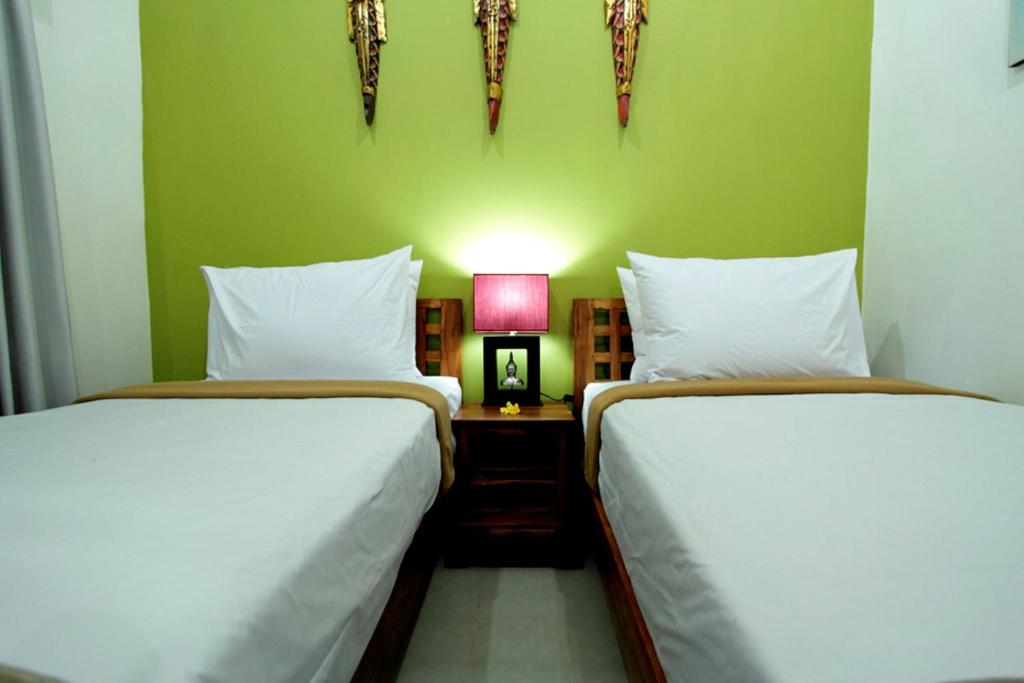 A bed or beds in a room at Maha Residence Guest House