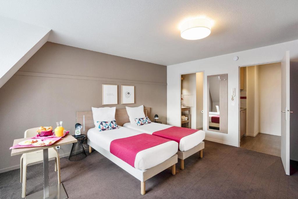 A bed or beds in a room at Appart'City Paris La Villette