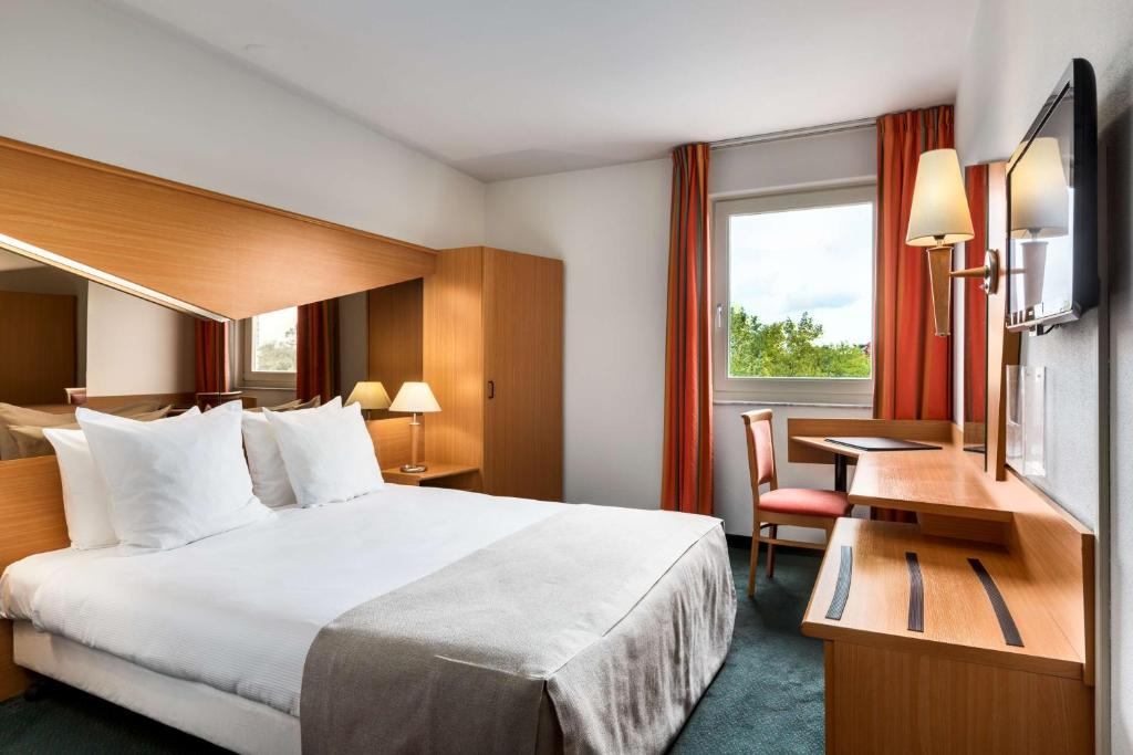 A bed or beds in a room at NH Best Hotel