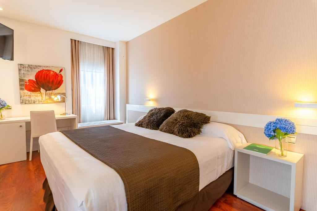 A bed or beds in a room at Amura Alcobendas