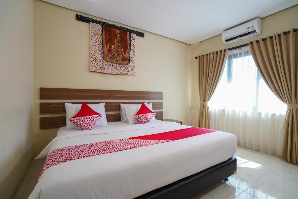 A bed or beds in a room at OYO 1992 China Town Hotel Bali