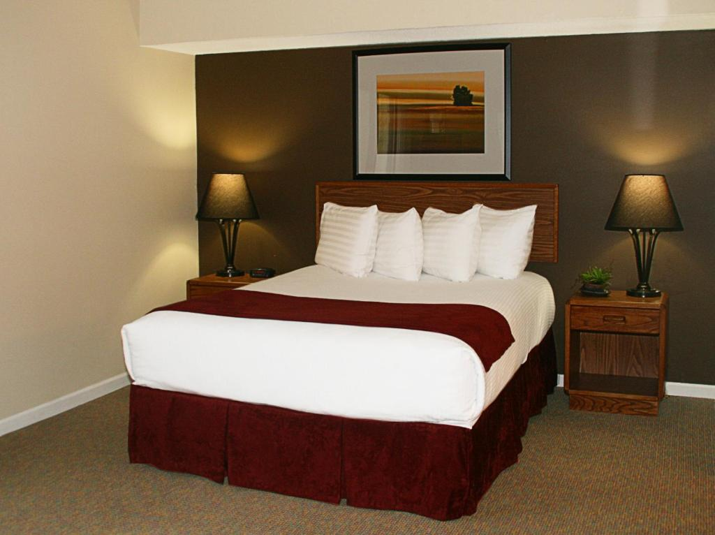 A bed or beds in a room at Sterling Hotel and Suites