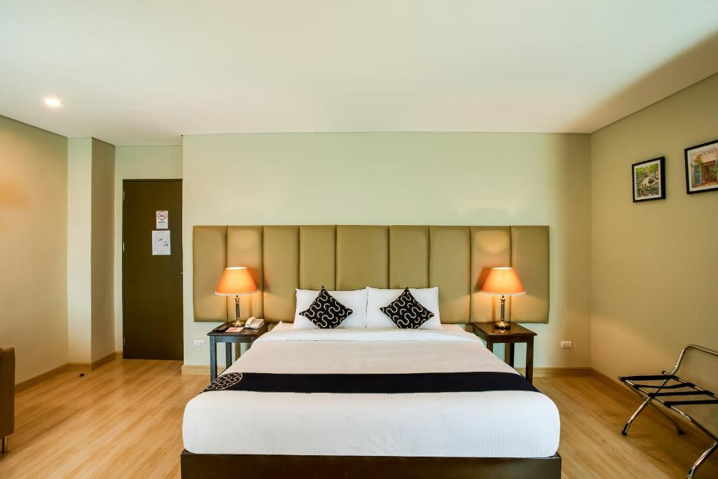 A bed or beds in a room at Capital O 461 Asrodel Hotel