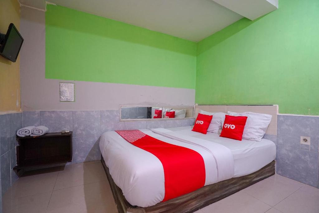 A bed or beds in a room at OYO 1495 Hotel Lendosis
