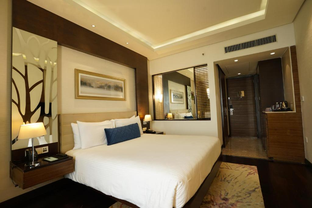 A bed or beds in a room at Hilton Garden Inn Gurgaon Baani Square