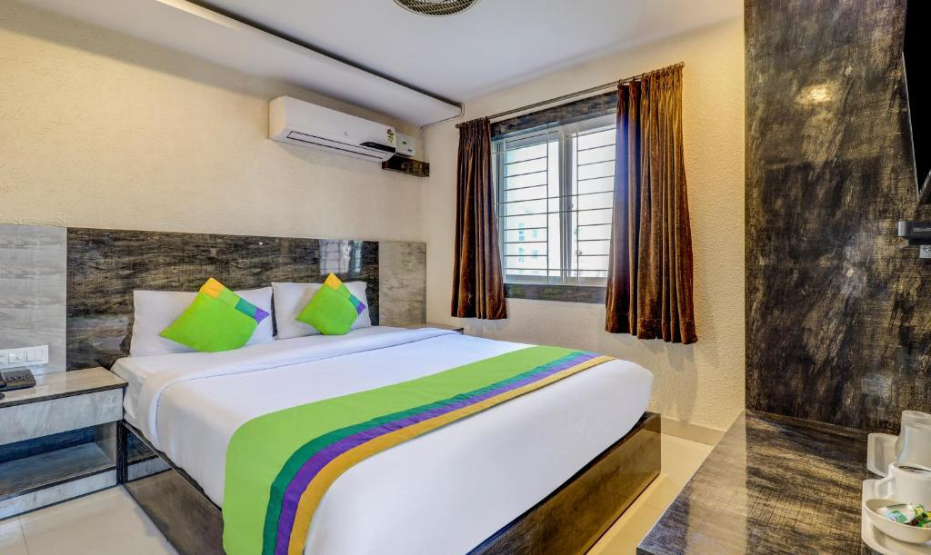 A bed or beds in a room at Treebo Trend Pride Homes Doddanakundi